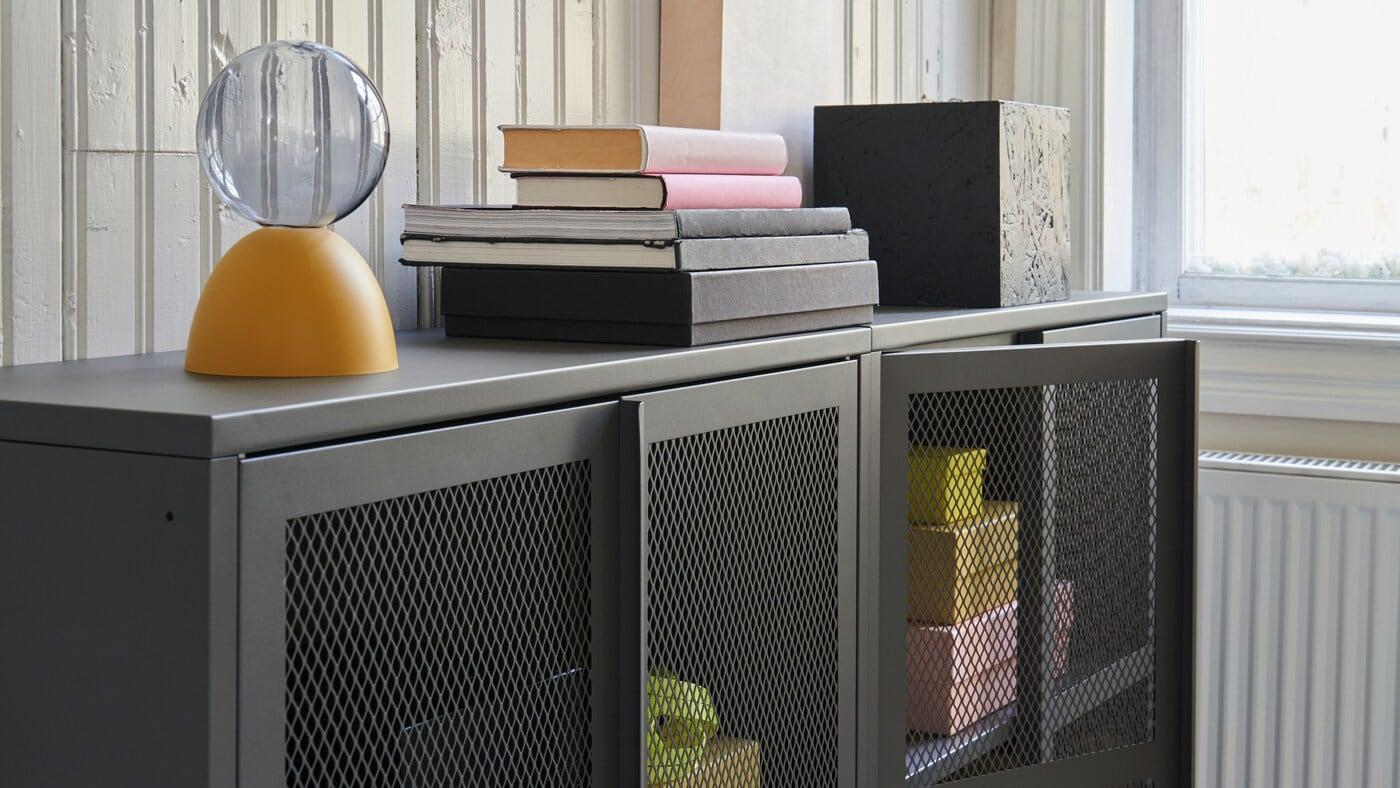 Dva skříňky IVAR z kovové síťoviny v šedé barvě, za průhlednými dvířky jsou vidět žluté a růžové předměty.