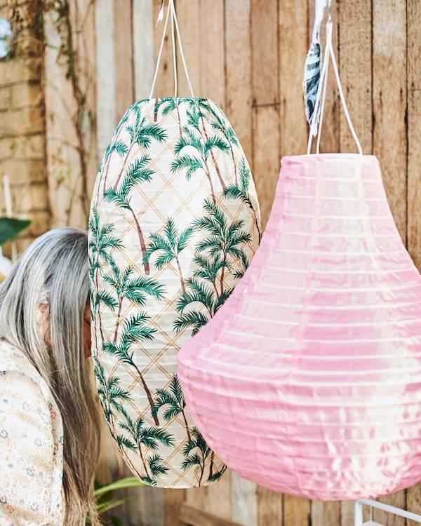 Dva velika viseća vanjska fenjera; jedan je roze boje, a drugi ima uzorak palmi. Fenjeri djelomično skrivaju ženu s dugom sijedom kosom.