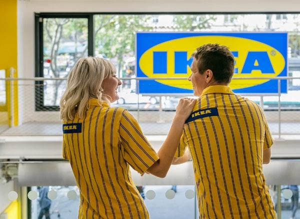 Dva zaměstnanci IKEA v žluto-modrých tričkách stojí v obchodním domě a povídají si.