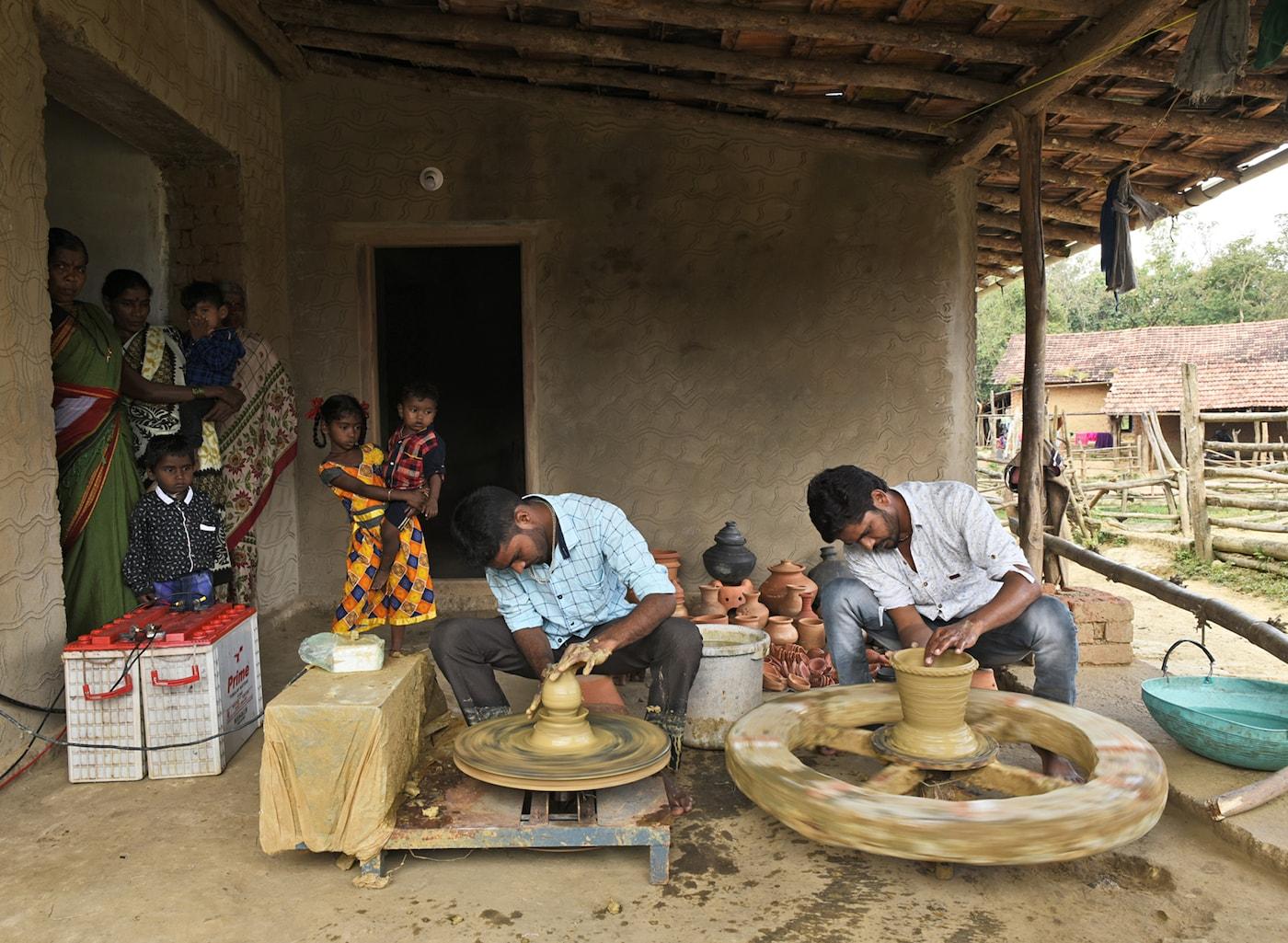 Dvaja indickí hrnčiari pracujú na hrnčiarskych kruhoch, zatiaľ čo ich pozorujú ostatní dedinčania.