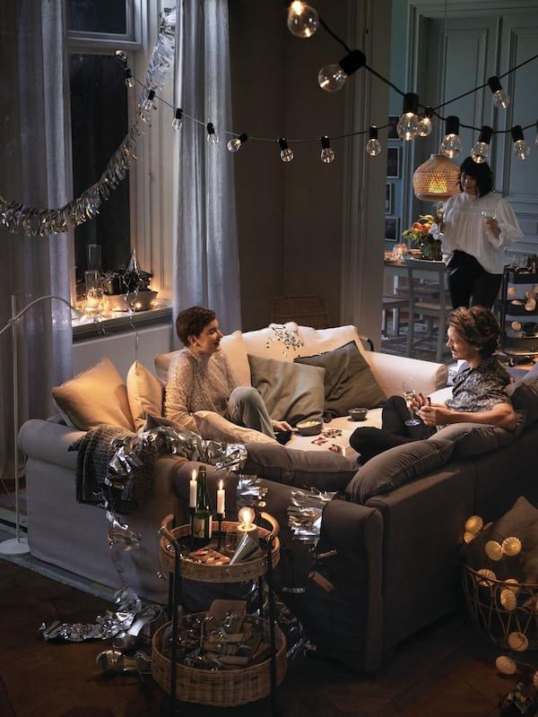 Dvaja ľudia sedia na dvoch pohovkách spojených uprostred miestnosti a smejú sa a rozprávajú.