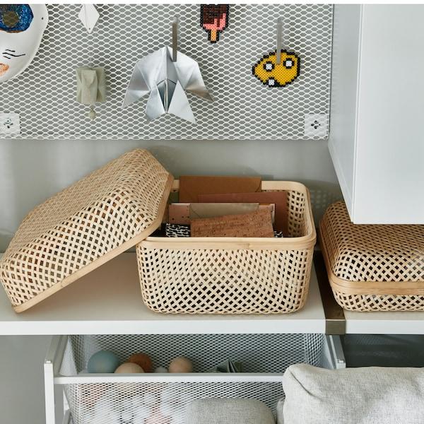 Dve bambusové škatule s vrchnákmi SMARRA položené na bielej polici, vrchnák väčšej škatule je otvorený a opretý zboku.