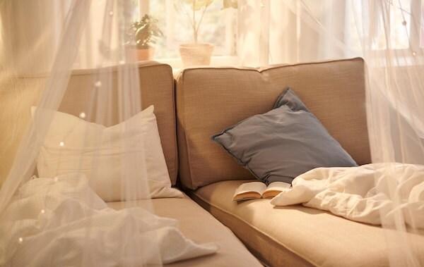 Dve béžové ležadlá KIVIK vedľa slnečného okna, na ktorých sú prikrývky a kniha, sieť SOLIG slúži ako baldachýn.