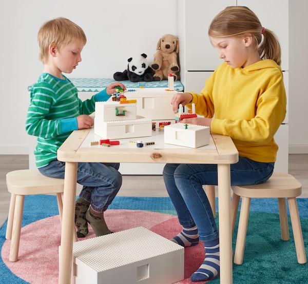 Dvě děti si hrají u dřevěného stolku s kostičkami lego, staví minifigurky LEGO na dvě bílé krabice BYGGLEK.
