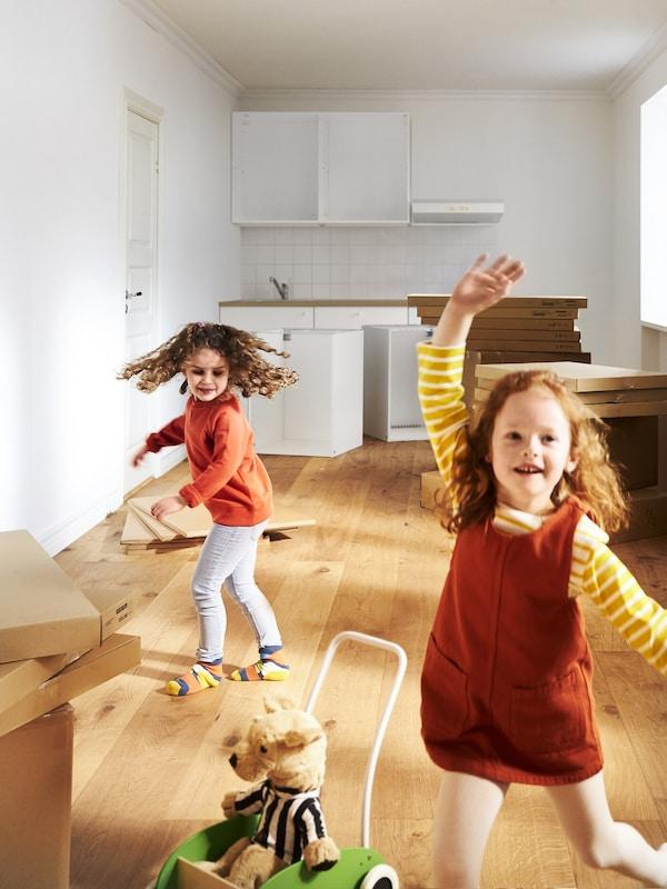 Dve dievčatká v červenom oblečení sa hrajú pri vybaľovaní v prázdnej kuchyni so škatuľami na sťahovami a plyšovou hračkou IKEA.
