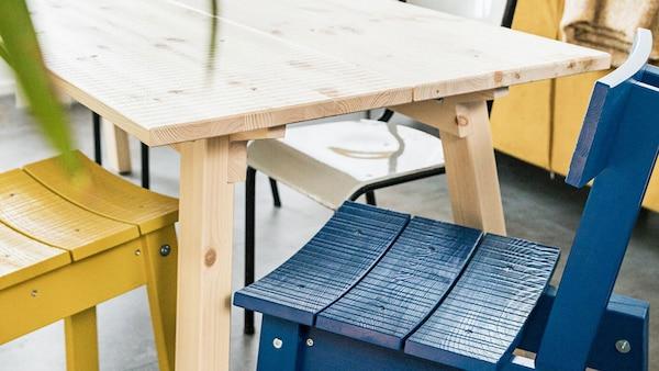 Dvě dřevěné židle IKEA INDUSTRIELL, jedna žlutá a druhá modrá, vyrobené z masivní borovice s úmyslnými nedokonalostmi.