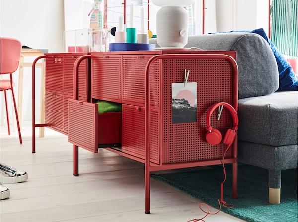 Dve IKEA NIKKEBY komode u crvenoj boji, s perforiranim površinama. Postavljene su iza sofe na razvlačenje u spavaćoj sobi.