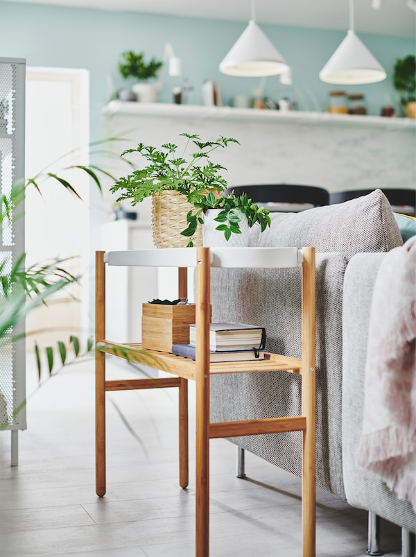 Dve male biljke u saksijama s laganim elementima za odlaganje na SATSUMAS stalku za biljke, pored sofe u dnevnoj sobi.