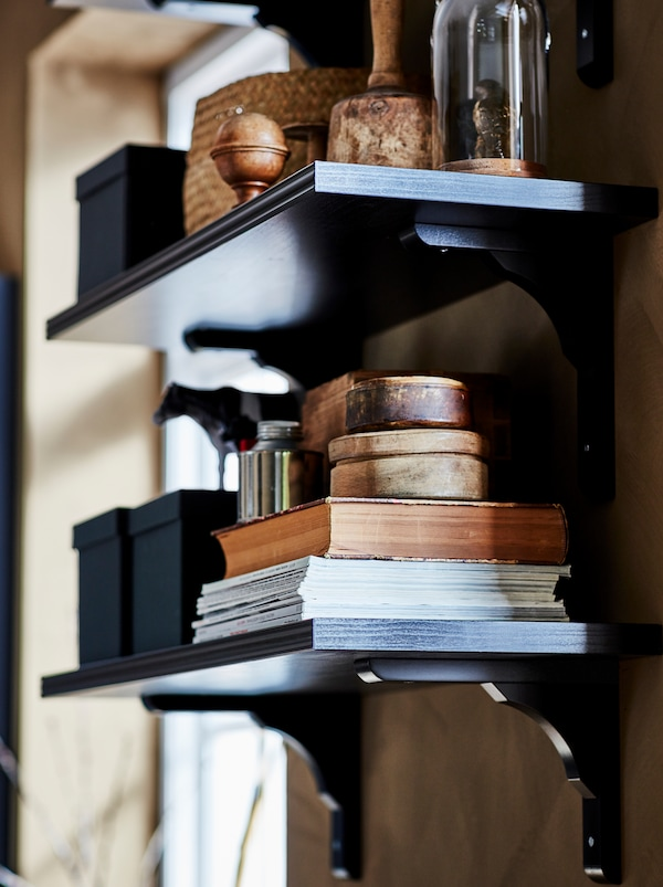 Dve nástenné čiernohnedé police BERGSHULT/RAMSHULT s knihami, škatuľami a dekoráciami.