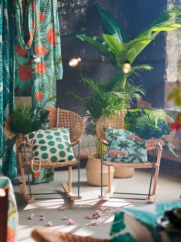 Dve ozdobené hojdacie kreslá GRÖNADAL vedľa seba s farebnými textíliami, tropickými rastlinami a kvetmi okolo.