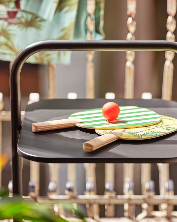 Две ракетки с желто-зеленым принтом и мяч лежат на черном столе, который стоит на балконе.