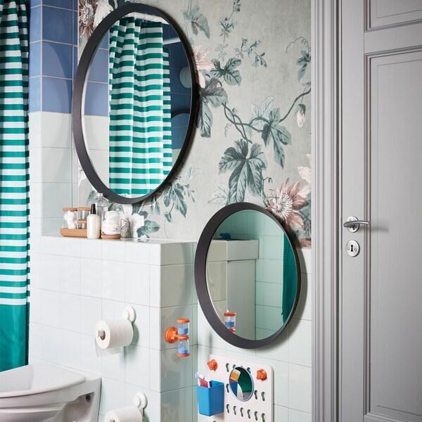 Dve rôzne veľké okrúhle zrkadlá zavesené v rozličnej výške na stene v kúpeľni s kvetovanou tapetou.