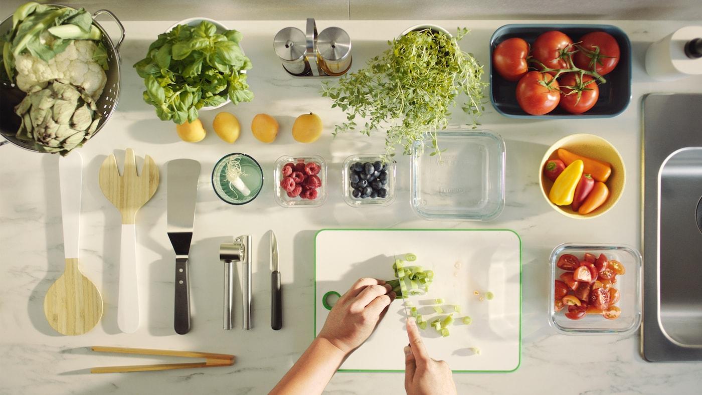 Две руки за нарезкой лука на бело-зеленой разделочной доске МАТЛЮСТ, рядом овощи, фрукты, пряные травы и кухонная утварь.