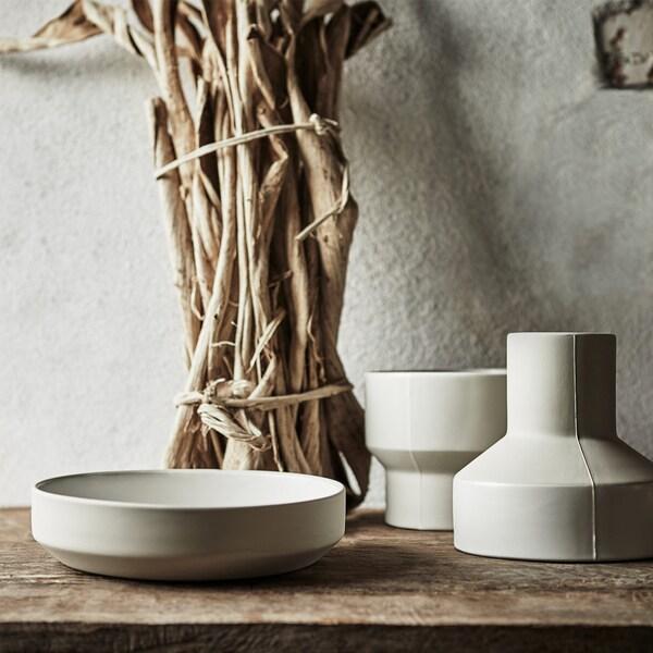 Dve svetlosivé ručne vyrobené keramické vázy a nízka, široká miska z kolekcie IKEA HANTVERK.