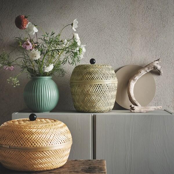 Dve TJILLEVIPS korpe od bambusa, s poklopcima, pored zelene vaze sa cvećem i drvenim grančicama.