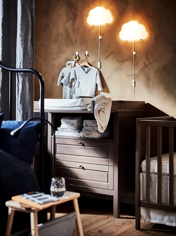 Dve UPPLYST LED zidne lampe u obliku oblaka iznad braon SUNDVIK drvenog stola za povijanje s dve fioke pored kreveca.