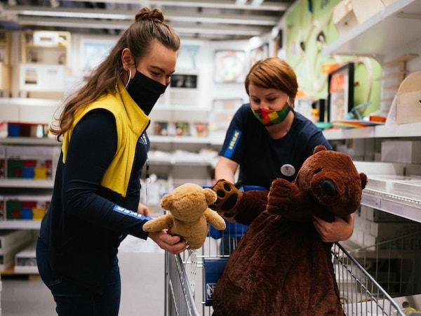 Dvě zaměstnankyně IKEA dávají plyšové medvídky do košíku.