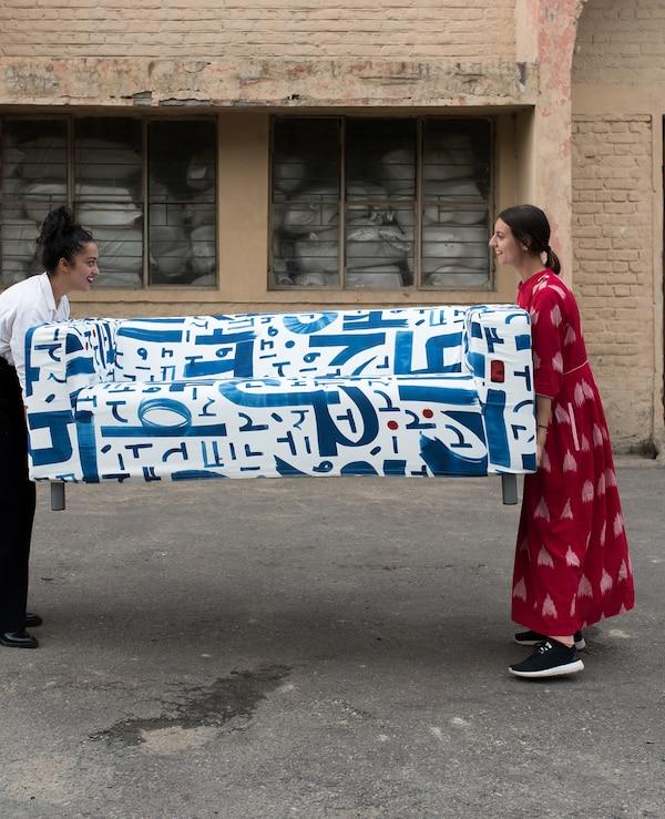 Dve žene drže krajeve sofe s plavim i belim tekstilom na asfaltu, ispred ciglanog magacina.