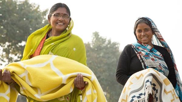 Dve ženy držia ručne tkané koberce IKEA.