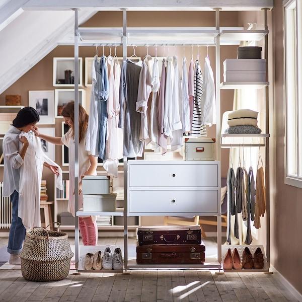 Dvě ženy upravující oblečení před otevřenou šatní skříní
