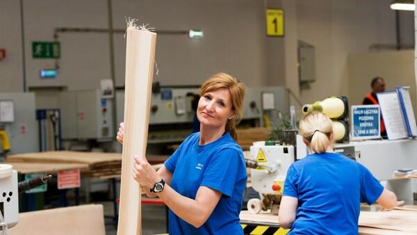 Dvě ženy v jasně modrých tričkách, které pracují s prototypy ve skladu dodavatelů IKEA.