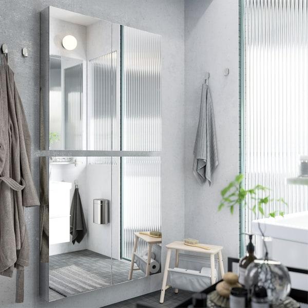 Дві дзеркальні шафи розміщені вертикально на сірій стіні ванної кімнати, що створює дзеркало у повний зріст.