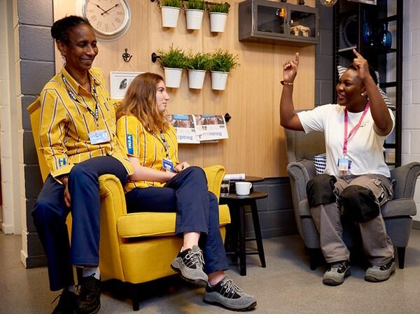 Дві співробітниці IKEA сидять на жовтому кріслі та слухають розповідь іншої співробітниці, яка діляться своїми цінностями та досвідом.