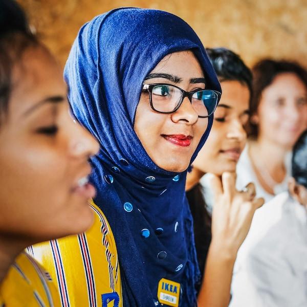 Дві співробітниці IKEA, які хочуть побудувати краще майбутнє для жінок Індії, уважно слухають промову.