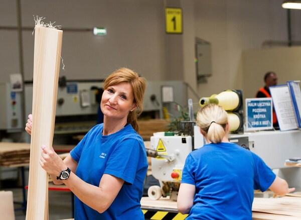 Дві жінки у яскраво-синіх футболках, які працюють зі зразками на складі постачальника IKEA.