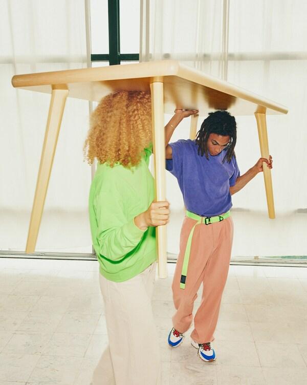 Двое молодых людей несут стол МАРКЕРАД, занеся его над головами.