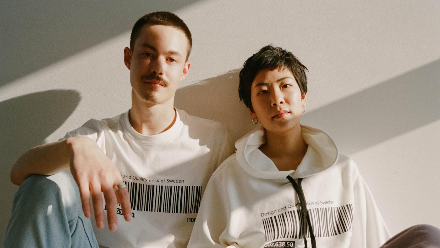 Dvojica oblečená v tričku a mikine z limitovanej kolekcie EFTERTRÄDA.