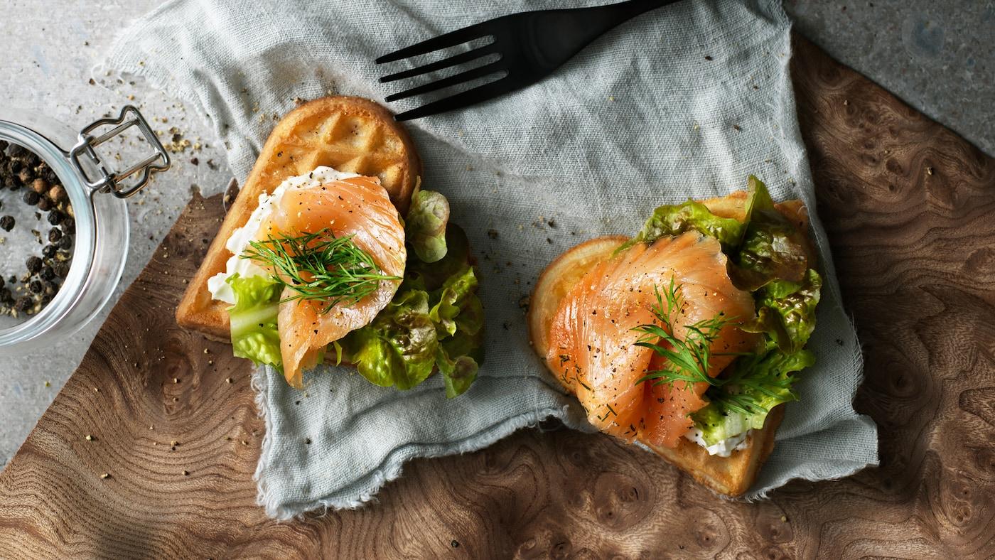 Dwa gofry VÅFFLOR w kształcie serca z łososiem, serem śmietankowym, koperkiem i sałatą na kawałku tkaniny obok widelca.
