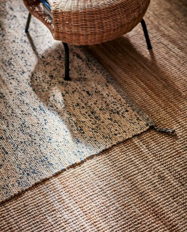 Dwa jutowe dywany, jeden większy, a drugi mniejszy z domieszką ciemnoniebieskiej wełny. Na dywanach stoi rattanowy podnóżek.