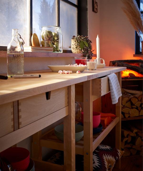 Dwa kuchenne wózki na kółkach pod ścianą, tworzące długi stolik; talerz ze słodyczami na zakończenie imprezy oraz świeca stoją na blacie.