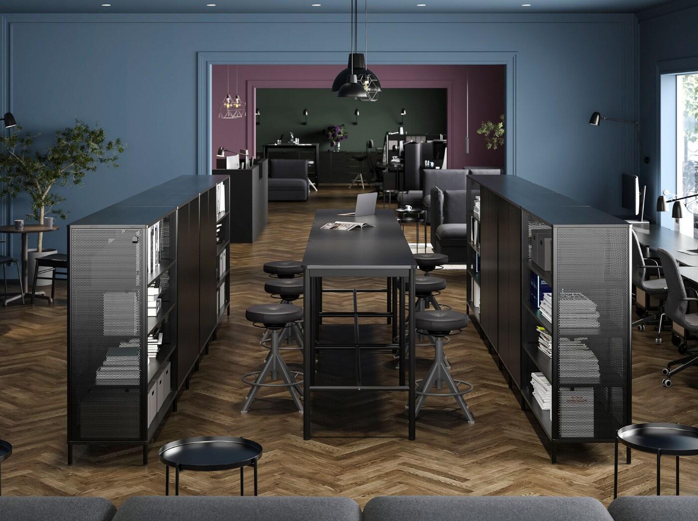 Dwa rzędy ustawionych na środku pomieszczenia czarnych regałów BEKANT z biurkami BEKANT i stołkami kreślarskimi TROLLBERGET pomiędzy nimi.