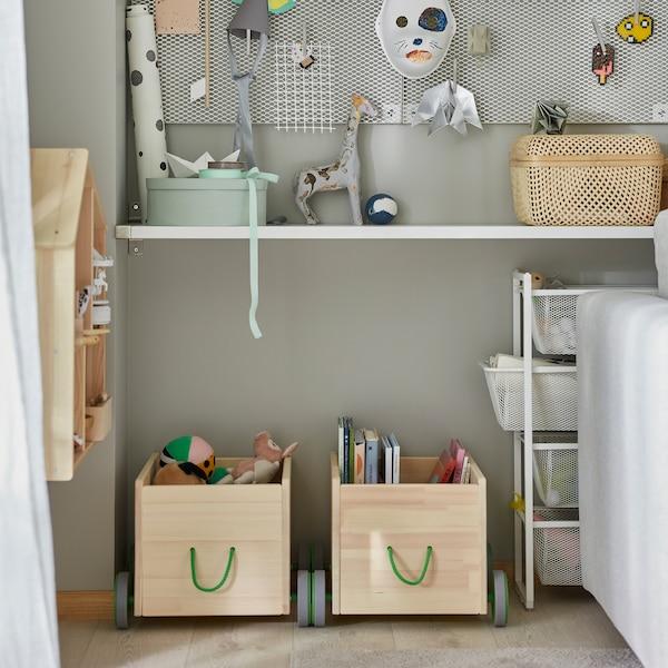 Dwa schowki na zabawki FLISAT z litej sosny z szarymi kółkami i zielonymi uchwytami, w których przechowywane są dziecięce książki i inne przedmioty.