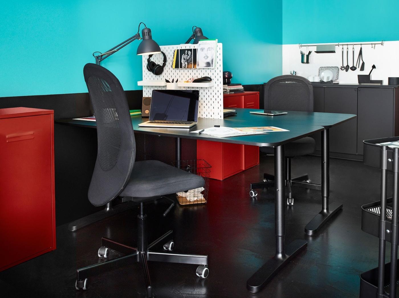 Dwa ustawione naprzeciwko siebie biurka rozdzielone tablicą perforowaną SKÅDIS. Każde z nich uzupełniono krzesłem FLINTAN, lampą biurkową TERTIAL i czerwoną szafką IVAR.