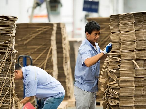 Dwaj mężczyźni sortujący kartony w zakładzie produkcyjnym dostawcy IKEA.