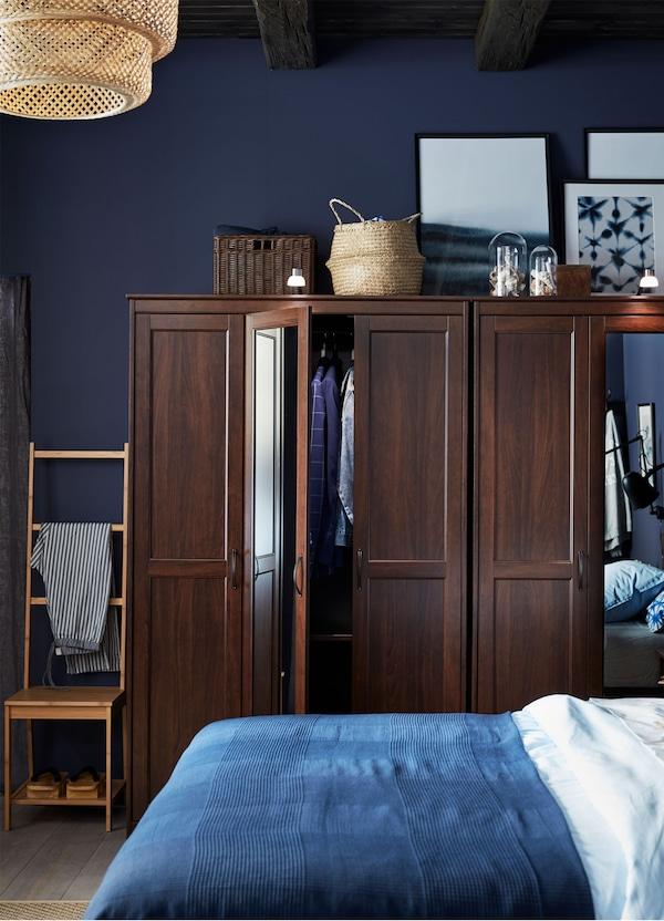 Dwie brązowe szafy IKEA SONGESAND z drzwiami z lustrem, za łóżkiem z niebieską i białą pościelą.