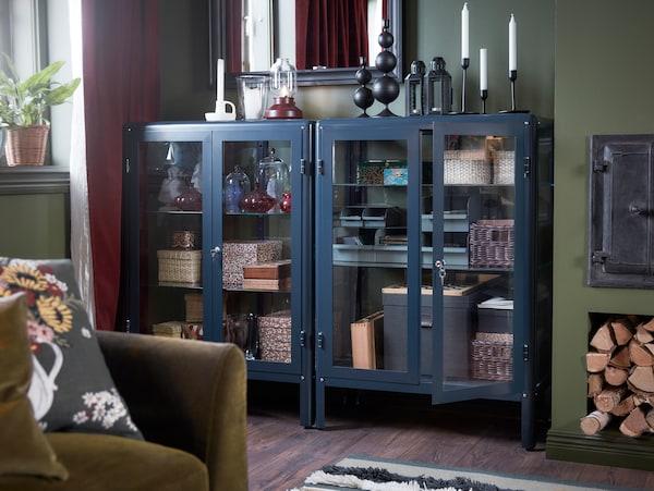 Dwie czarnoniebieskie witryny z ustawionymi na nich świeczkami i poukładanymi wewnątrz ozdobnymi pudełkami. Nad witrynami wisi lustro.