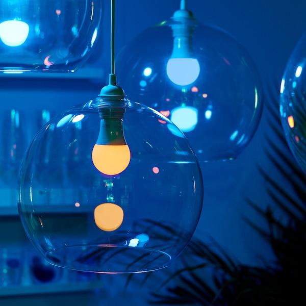 Dwie lampy wiszące JAKOBSBYN z żarówkami TRÅDFRI z funkcją przyciemniania. Lampy są włączone i emitują niebieskie światło.