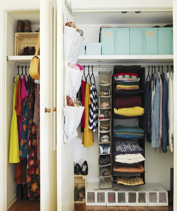 Dwie otwarte wbudowane szafy z wiszącymi rozwiązaniami do przechowywania i pudełkami wypełnionymi kolorowymi ubraniami i butami.