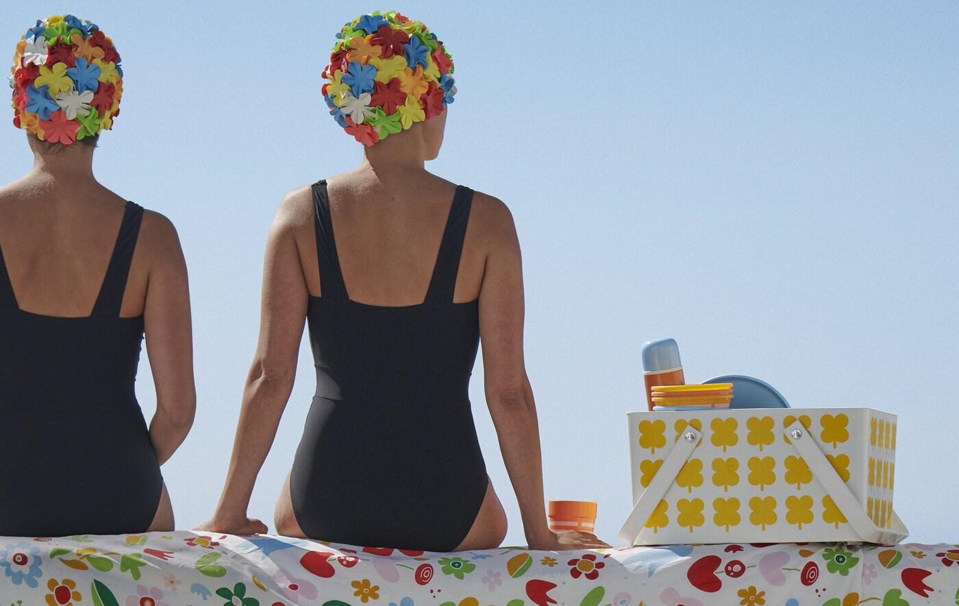 Dwie pływaczki siedzą na wzorzystej tkaninie obok pojemnika piknikowego.