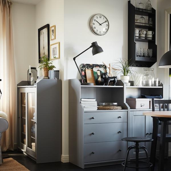 Dwie szare komody z półkami, na których poustawiano ozdoby, okrągły stolik, czarne krzesło i czarna lampa wisząca.