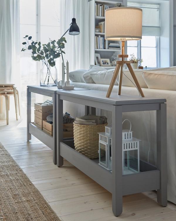 Dwie szare ławy ustawione za sofą i pełniące funkcję ozdobnych ścianek działowych. Dwie lampy stołowe ustawione na górze.