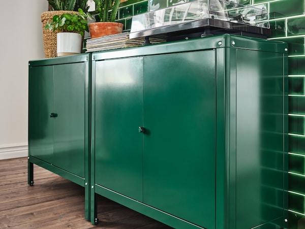 Dwie zielone szafki ustawione pod wyłożoną zielonymi płytkami ścianką. Na szafkach znajdują się zielone rośliny, sterta płyt winylowych i gramofon.