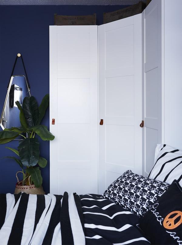 دولاب ملابس زاوية بيضاء في غرفة نوم زرقاء.