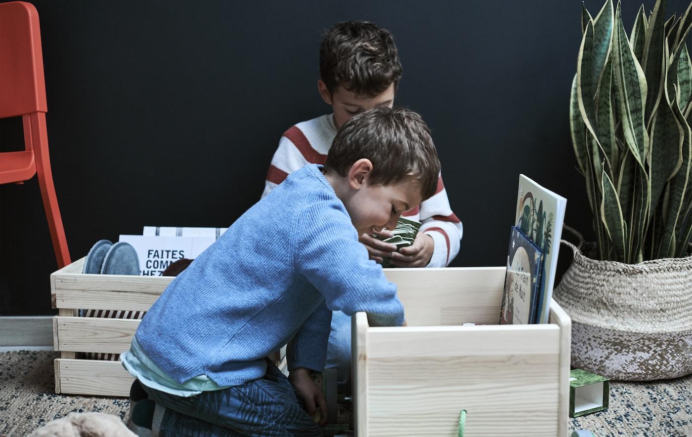 Dwóch chłopców zaglądających do drewnianego pudełka wypełnionego różnymi drobiazgami.