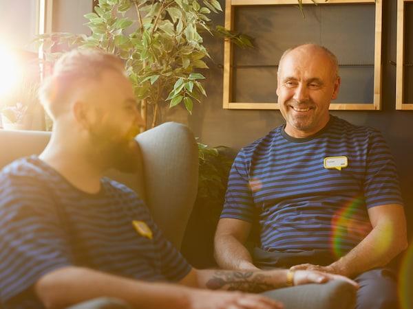 Dwóch pracowników IKEA siedzących na fotelch i rozmawiających ze sobą.