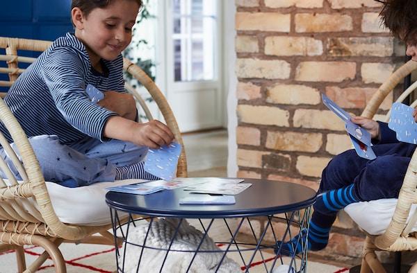 Dwójka dzieci siedzi na rattanowych fotelach po przeciwnych stronach stolika kawowego, pochłonięta grą w karty.